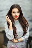 Close-up portrait of a stylish and very beautiful brunette girl, red lipstick, street style royalty free stock image