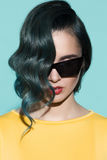 Close-up portrait of stylish woman in sunglasses. On a blue background Royalty Free Stock Photos