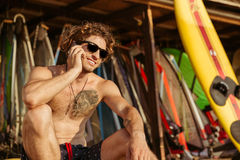 Close up portrait of a surfer man talking on smartphone. Close up portrait of a young handsome surfer man in eyeglasses sitting and talking on smartphone Royalty Free Stock Images