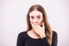 Close-up portrait of surprised attractive woman covering her mouth by the hands, over white background royalty free stock image