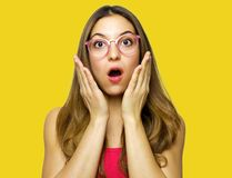 Close-up portrait of surprised beautiful girl holding her head in amazement and open-mouthed. Over yellow background stock image