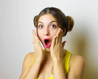 Close-up portrait of surprised beautiful girl holding her head i royalty free stock photo