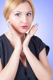 Close-up portrait of surprised beautiful woman. On blue background Royalty Free Stock Images