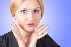 Close-up portrait of surprised beautiful woman. On blue background Stock Photo