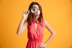Close-up portrait of surprised beautiful woman looking at camera. Through magnifying glass, isolated over yellow background Royalty Free Stock Photo