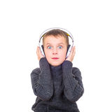 Close up portrait of surprised boy listening to music with headp Royalty Free Stock Photos