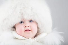 Close up portrait of a sweet baby in a white fur hat Stock Photos