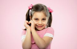Close Up Portrait Of A Sweet Child Girl With Shallow Depth Of Field Doing Heart Gesture, On Pink stock photos