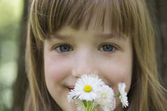 Close up portrait of a sweet little girl with flowers in her han Stock Images