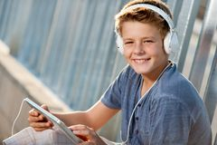 Close up portrait of teen boy with tablet. Close up portrait of handsome teen boy with tablet and headphones Royalty Free Stock Photos