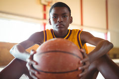 Close up portrait of teenage boy with ball sitting on floor Royalty Free Stock Images