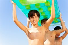 Smiling boy carrying swimming mattress over head. Close-up portrait of teenage boy carrying swimming air mattress over head together with his friends royalty free stock photography