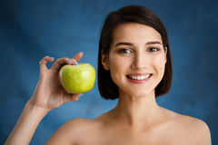 Close up portrait of tender young girl holding apple over blue background stock photography