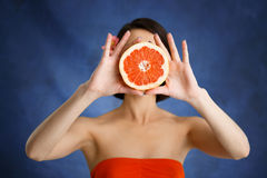 Close up portrait of tender young girl holding cut orange over blue background stock photos