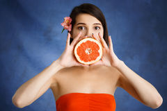 Close up portrait of tender young girl holding cut orange over blue background stock photo