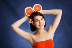Close up portrait of tender young girl holding cut orange over blue background. Picture of tender young girl holding orange over blue background Stock Image