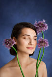 Close up portrait of tender young girl with lilac flowers over blue background stock photos