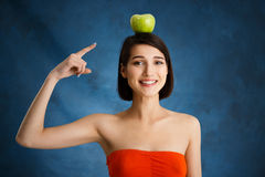 Close up portrait of tender young girl pointing with finger at apple on her head over blue background royalty free stock image