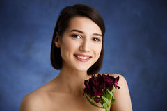 Close up portrait of tender young girl with red flowers over blue background stock image