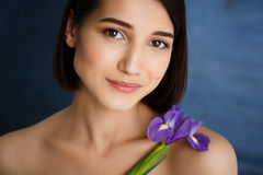 Close up portrait of tender young girl with violet flower over blue background royalty free stock photography