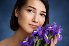 Close up portrait of tender young girl with violet irises over blue background Stock Image