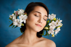 Close up portrait of tender young girl with white flowers over blue background royalty free stock image