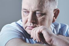 Thinking man headshot. Close up portrait of thoughtful aged man in t-shirt sitting with hand on chin - depression concept stock photo