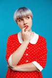 Close up portrait thoughtful beautiful dollish girl with short light violet hair wearing red dress over blue background. Royalty Free Stock Image