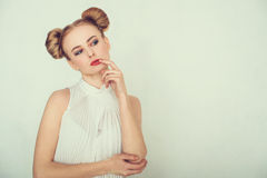 Close-up portrait of thoughtful beautiful girl. with funny hairstyle. Sly and scheming young woman face expression. Royalty Free Stock Photography