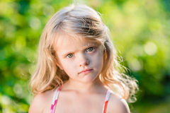 Close-up portrait of thoughtful little girl with long blond hair. Sunny summer day in beautiful park Stock Photo