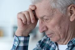 Portrait of thoughtful senior man at home royalty free stock photo