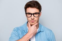 Close up portrait of thoughtful, stunning, virile, harsh man in. Jeans shirt, glasses touching chin with fingers, looking at camera,  on grey background Royalty Free Stock Images