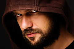 Close-up portrait of threatening man with beard wearing a hood. Against gray background stock photos