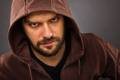 Close-up portrait of threatening man with beard wearing a hood Royalty Free Stock Photo