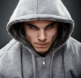 Close-up portrait of threatening thug. Close-up portrait of threatening gangster wearing a hoodie, representing the concept of danger stock image