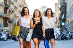 Three happy female shoppers in city. stock photos