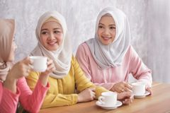 Three beautiful siblings having an a coffee time together. Close up portrait of three beautiful siblings having an a coffee time together Stock Images