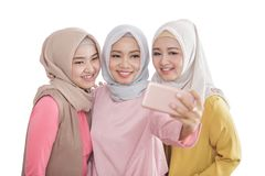 Three beautiful siblings taking selfies using mobilephone camera. Close up portrait of three beautiful siblings taking selfies using mobilephone camera isolated Royalty Free Stock Images