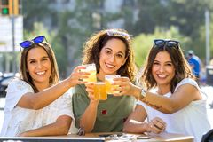 Three girl friends having a drink together on terrace. royalty free stock photography