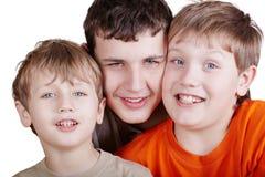 Close-up portrait of three grinning boys. Head to head, cheek to cheek stock photos