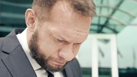 Close-up portrait of a tired business man muttering something.  stock video
