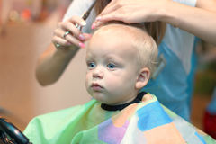 Close up portrait of toddler child getting his first haircut.  Royalty Free Stock Photos