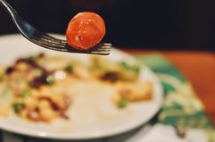 Close-up portrait of tomato on the fork with blurry background of salad. Healthy and vegan food concept Royalty Free Stock Images