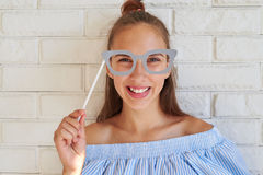 Close-up portrait of toothy smile girl having fun while holding. A paper glasses on a stick Stock Photo