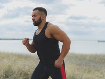 A close-up of a sportive jogger on a natural background. A handsome bodybuilder running outdoors. Sports concept. royalty free stock photos
