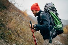 Close up portrait of traveler bearded man trekking and mountaineering during his journey. Side view of young male hiking in mountains. Travel, people, sport royalty free stock photos