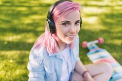 Close up portrait of trendy hipster Caucasian beautiful young woman with pink hair in headphones listening to music stock images