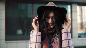 Close-up portrait of a trendy young woman in hat and autumn coat against a background of urban architecture.  stock video