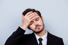 Close up portrait of troubled unhappy man in formal-wear touching his forehead because of having high temperature royalty free stock photography