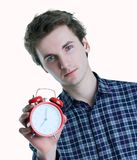 Close-up portrait of a troubled young man holding alarm clock isolated over white background. Late for work, bad sleep royalty free stock images
